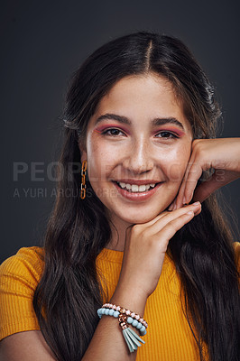 Buy stock photo Cropped portrait of an attractive teenage girl standing alone against a dark studio background with her hands to her face
