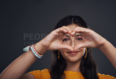 Buy stock photo Cropped portrait of an attractive teenage girl making a heart-shaped hand gesture against a dark studio background