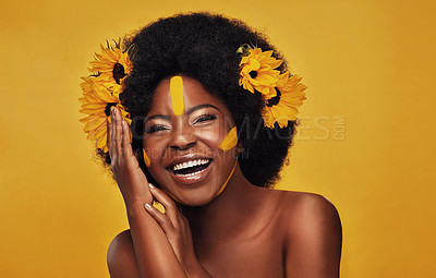 Buy stock photo Studio portrait of a beautiful young woman smiling while posing with sunflowers in her hair against a mustard background