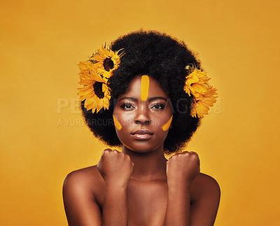Buy stock photo Studio portrait of a beautiful young woman posing topless with sunflowers in her hair against a mustard background