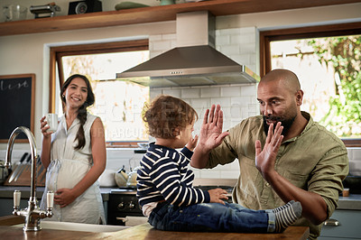 Buy stock photo Shot of a young man giving his adorable child a high five at home.