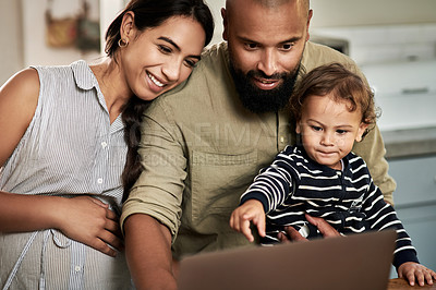 Buy stock photo Shot of a happy young family using a laptop together at home