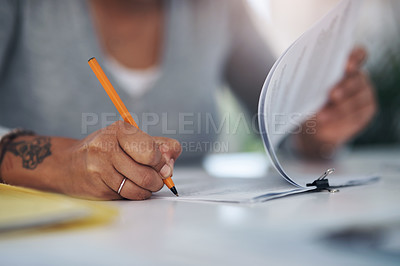 Buy stock photo Cropped shot of an unrecognizable businesswoman sitting alone in her office and writing on paperwork