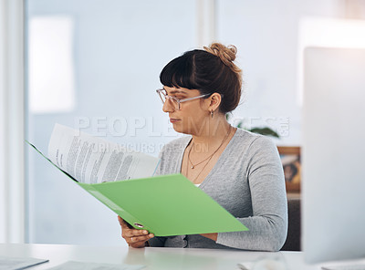 Buy stock photo Cropped shot of an attractive young businesswoman sitting alone in her office and reading through paperwork