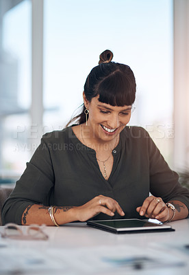 Buy stock photo Cropped shot of an attractive young businesswoman sitting alone in her office and using a tablet