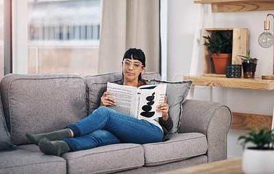Buy stock photo Full length shot of an attractive young woman sitting alone in her living room and reading a book