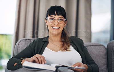 Buy stock photo Cropped portrait of an attractive young woman sitting alone in her living room and reading a book