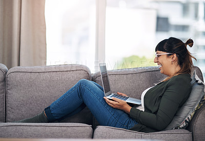 Buy stock photo Full length shot of an attractive young woman sitting alone in her living room and using her laptop
