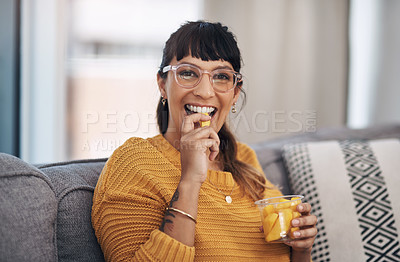 Buy stock photo Cropped portrait of an attractive young woman sitting alone in her living room and enjoying mangoes during a day off