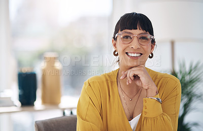 Buy stock photo Cropped portrait of an attractive young businesswoman sitting alone in her office with her hand on her chin