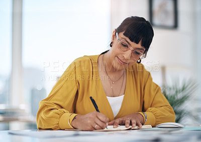 Buy stock photo Cropped shot of an attractive young businesswoman sitting alone in her office and writing in a notebook