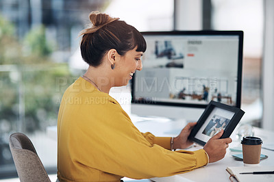 Buy stock photo Cropped shot of an attractive young businesswoman sitting alone in her office and looking at a picture frame