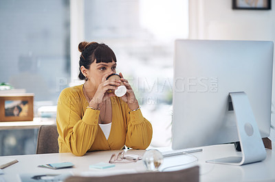 Buy stock photo Cropped shot of an attractive young businesswoman sitting in her office and enjoying a coffee while using her computer