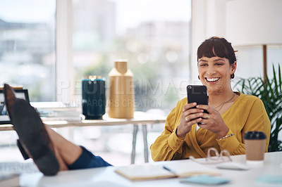 Buy stock photo Cropped shot of an attractive young businesswoman sitting with her feet up in her office and using her cellphone