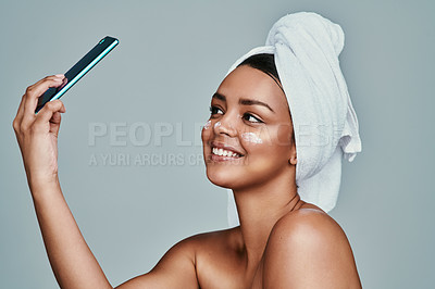 Buy stock photo Shot of a woman taking a selfie with a towel wrapped around her hair and moisturizer on her face