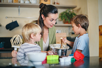 Buy stock photo Shot of a young woman baking with her two adorable sons at home