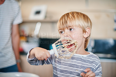 Buy stock photo Shot of an adorable little boy licking the batter from a whisk while baking at home