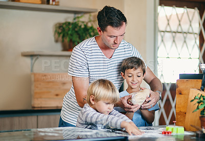 Buy stock photo Shot of a young man baking with his two adorable sons at home