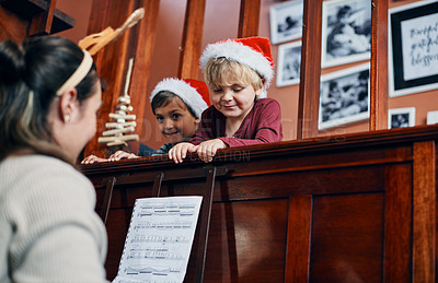 Buy stock photo Shot of a young woman playing the piano for her sons at Christmas