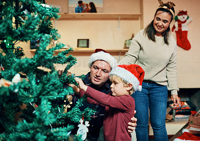 Buy stock photo Shot of an adorable little boy decorating the Christmas tree with his father at home