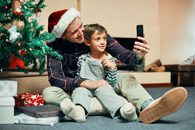 Buy stock photo Shot of an adorable little boy taking selfies with his father while unwrapping Christmas presents at home