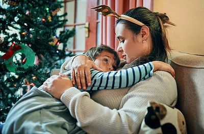 Buy stock photo Shot of an adorable little boy relaxing on the sofa with his mother at Christmas