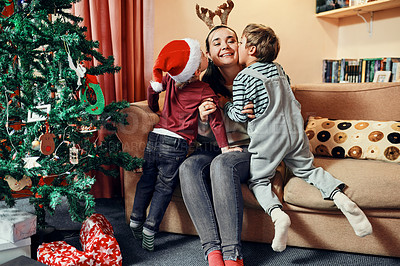 Buy stock photo Shot of two adorable little boys given their mother kisses during Christmas at home