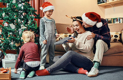 Buy stock photo Shot of a young woman receiving a Christmas present from her family
