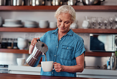Buy stock photo Cropped shot of an attractive senior woman pouring herself a cup of coffee while standing in the kitchen