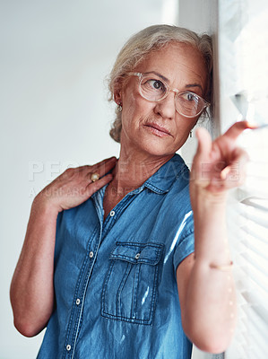 Buy stock photo Cropped shot of an attractive senior woman looking out of her window at home