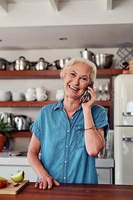 Buy stock photo Cropped portrait of an attractive senior woman making a phonecall while preparing breakfast in the kitchen at home