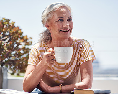 Buy stock photo Cropped shot of an attractive senior woman enjoying her breakfast while sitting outside on the balcony at home