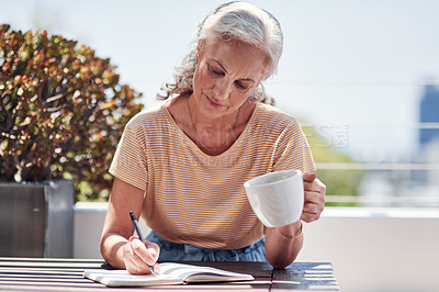 Buy stock photo Cropped shot of an attractive senior woman enjoying a cup of coffee while writing in her book outside on the balcony at home
