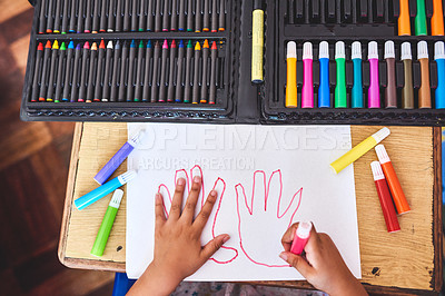 Buy stock photo Cropped shot of an unrecognizable little girl drawing hands on a page at home