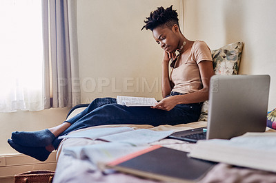 Buy stock photo Shot of an attractive young female university student reading a textbook in her room