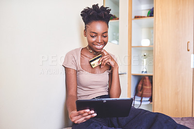 Buy stock photo Cropped shot of an attractive young female university student using a credit card and a digital tablet to shop online in her room