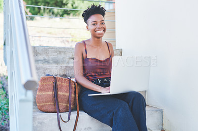Buy stock photo Cropped portrait of an attractive young female university student using a laptop while sitting outside her residence during the day