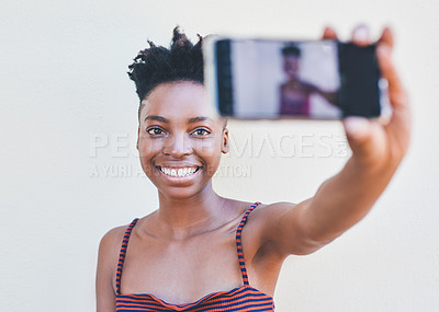 Buy stock photo Cropped portrait of an attractive young female university student taking a selfie while standing against a grey background