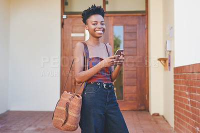 Buy stock photo Cropped portrait of an attractive young female university student smiling while using a smartphone outside her residence