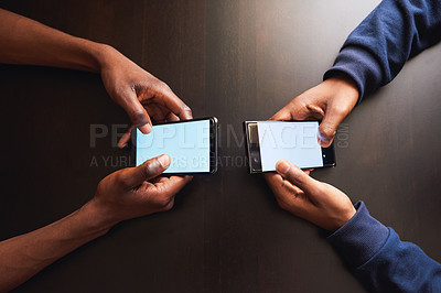 Buy stock photo High angle shot of two unrecognizable people browsing on their cellphones while being seated at a table
