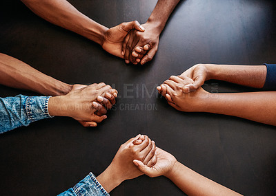 Buy stock photo High angle shot of a group of unrecognizable people holding hands while being seated at a table