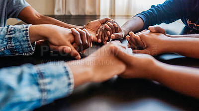 Buy stock photo Closeup of a group of unrecognizable people holding hands while being seated at a table