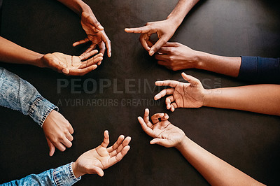 Buy stock photo High angle shot of a group of unrecognizable people gesturing with their hands in a circles while being seated at a table