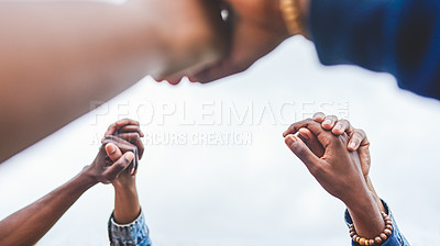 Buy stock photo Cropped shot of a group of unrecognizable people holding each other's hands in the air outside during the day