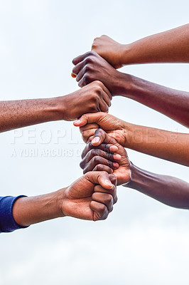 Buy stock photo Cropped shot of a group of people stacking their fists on top of each other's fists outside during the day