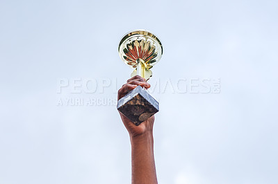 Buy stock photo Cropped shot of an unrecognizable person holding up a trophy in the air outside during the day