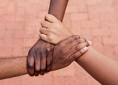 Buy stock photo High angle shot of a group of unrecognizable people holding hands and making a huddle outside during the day