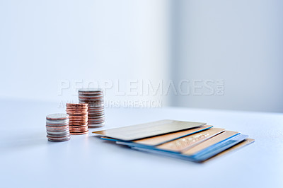 Buy stock photo Closeup of a collection of credit cards placed next to stacks of coins on top of a counter top inside during the day