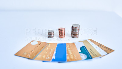 Buy stock photo Closeup of a collection of credit cards placed next to stacks of coins on top of a white surface inside during the day