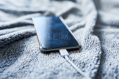 Buy stock photo Closeup of a cellphone being charged on top of a bed inside during the day